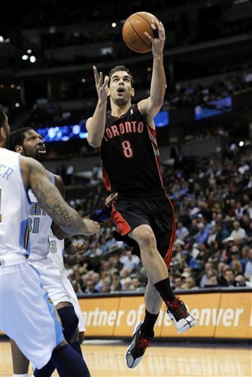 Toronto Raptors guard Jose Calderon (8), from Spain, goes up for a shot against Denver Nuggets center Nene (31), from Brazil, during the first quarter of an NBA basketball game in Denver Monday, March 21, 2011. (AP Photo/Jack Dempsey)