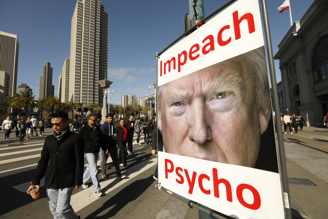 An anti-Trump poster is mounted on a lamppost along San Francisco's Embarcadero