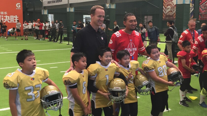 Participants in a football clinic take a photo with retired NFL quarterback Peyton Manning.