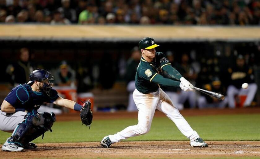 Matt Chapman de los Atléticos de Oakland batea ante Mike Zunino (i) de los Marineros durante un partido de béisbol de la MLB, entre los Marineros de Seattle y los Atléticos de Oakland, en el Coliseo de Oakland, California (EE.UU.). EFE