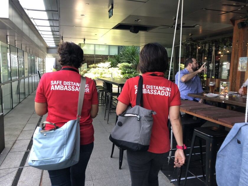 Safe-distancing ambassadors Rugayah Noordin and Fiona Tay, right, walk past a bar in Singapore.