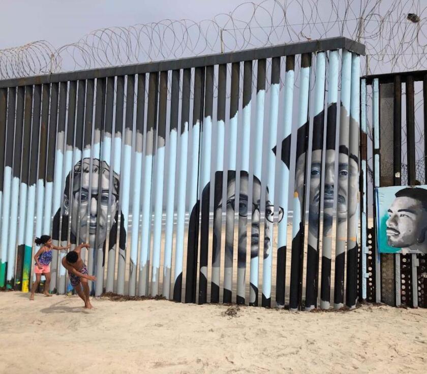Dos niños juegan frente a un nuevo mural en el lado mexicano del muro fronterizo en Tijuana, México,