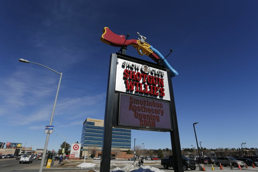 In this Feb. 10, 2016 photo, a large roadside sign marks the entrance of longtime strip club Shotgun Willie's, and Smoking Gun Apothecary, the new marijuana dispensary, in Glendale, Colo.   Smokin Gun Apothecary is on a site formerly occupied by the Denver area's best known strip club, Shotgun Will