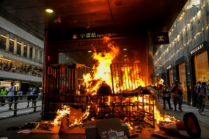 Fire set by protesters blocks the entrance to the MTR Central station stop in Hong Kong on Sunday.