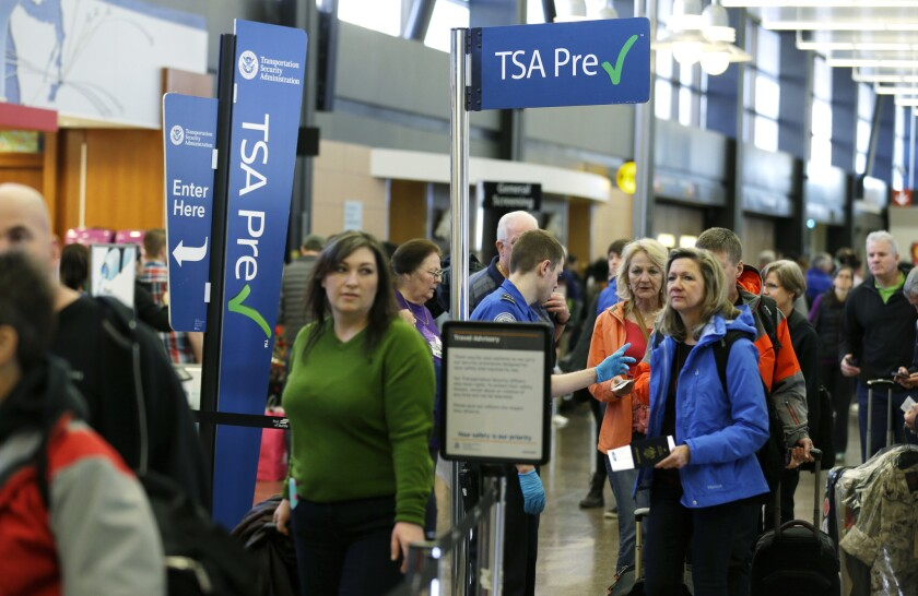 Travelers authorized to use the TSA PreCheck expedited security line at Seattle-Tacoma International Airport in Seattle have their documents checked by Transportation Security Administration workers. Critics say the TSA PreCheck program has yet to enroll enough members to reduce overall airport wait times.