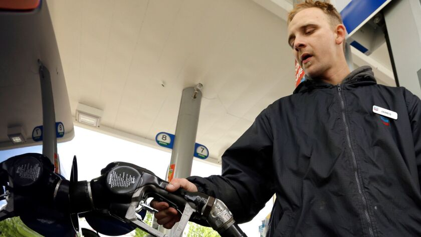 FILE - In this May 6, 2015 file photo, attendant James Lewis pumps gas at a station in Portland, Ore