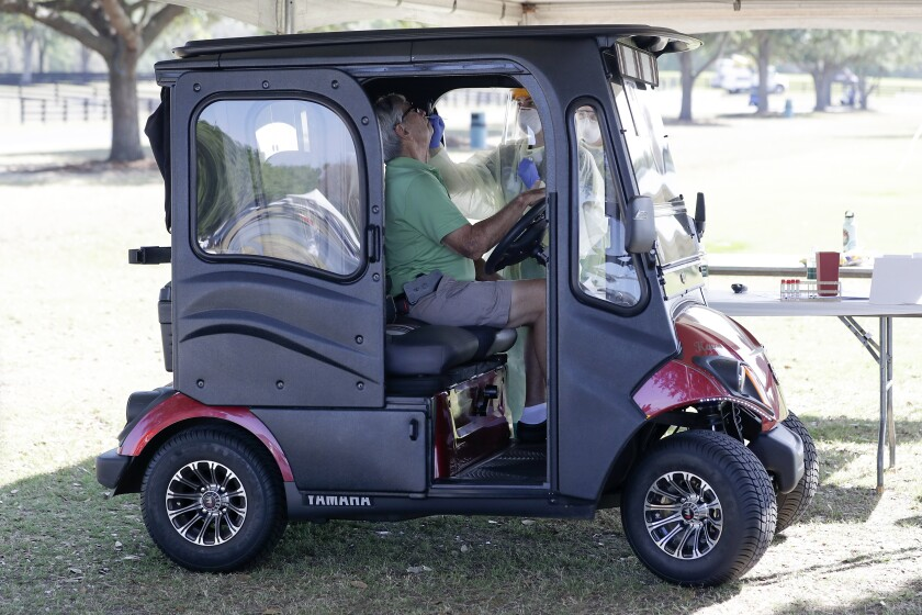 A resident in a golf cart is tested for COVID in the Villages, Fla.