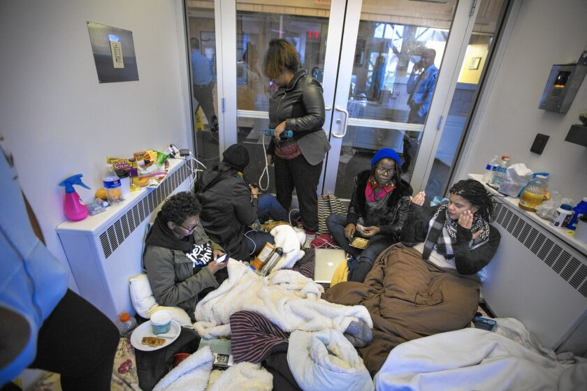 Demonstrators camp out in the lobby of Minneapolis Police Department's 4th precinct station, after officers shot and critically wounded a man over the weekend.