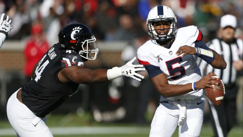 Connecticut quarterback David Pindell (5) is pressured by Cincinnati defensive end Marquise Copeland
