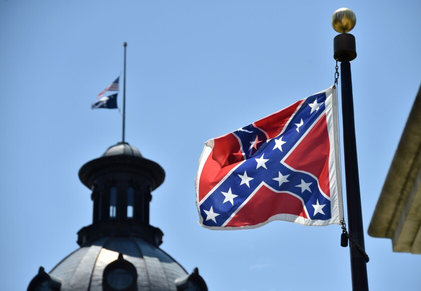 The U.S. and South Carolina flags are seen flying at half-staff behind the Confederate flag, which is erected at a war memorial on the South Carolina Capitol grounds. Controversy over displaying the Confederate flag, which some say is a symbol of white supremacy and hatred, has ensued after the Charleston, S.C., shooting.
