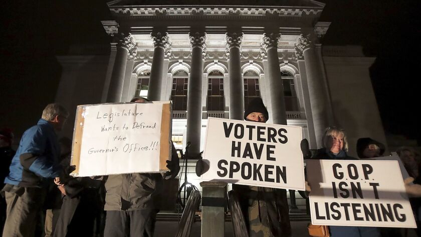 Opponents of an extraordinary session bill submitted by Wisconsin Republican legislators gather for a rally outside the Wisconsin State Capitol in Madison, Wis., on Monday.