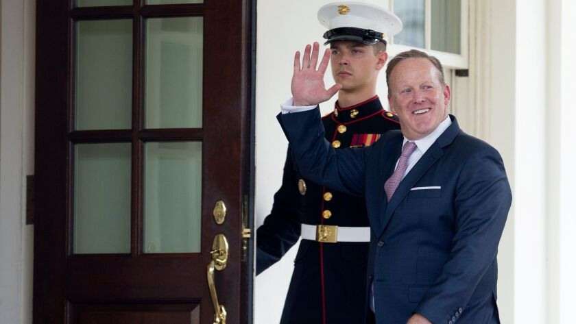 Outgoing White House Press Secretary Sean Spicer waves beside a US Marine as he enters the West Wing of the White House on July 21, 2017.