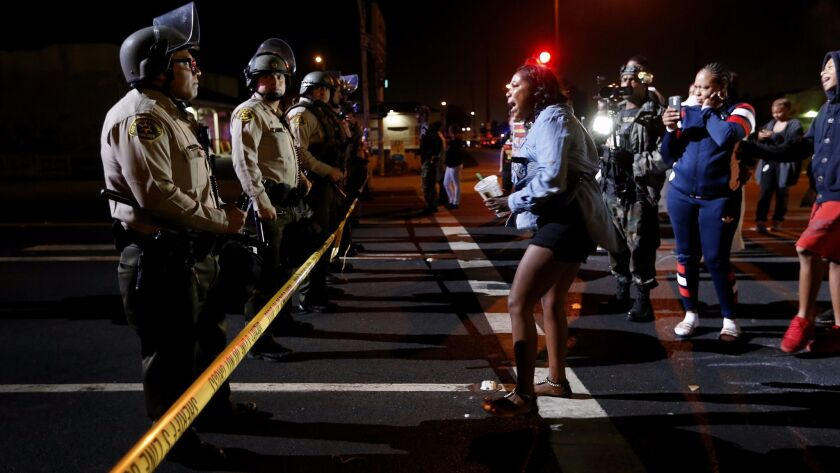 A women confronts the LA County Sheriif blocking the street after a vigil is held for Carnell Snell