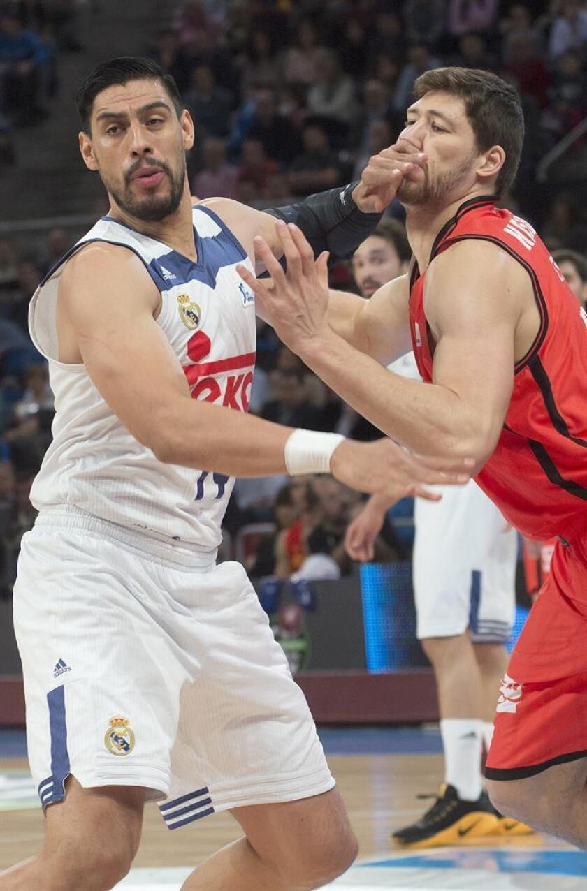 Los pivots del Real Madrid, el mexicano Gustavo Ayón (i) y del Valencia Basket, el ucraniano Viacheslav Kravtsov, pelean durante el encuentro correspondiente a la final de Copa del Rey, que disputaron en el Fernando Buesa Arena de Vitoria. EFE
