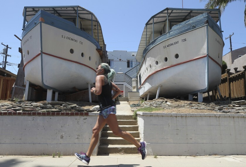 A woman jogs past the Encinitas Boathouses, located on Third Street, on Wednesday, July 31.