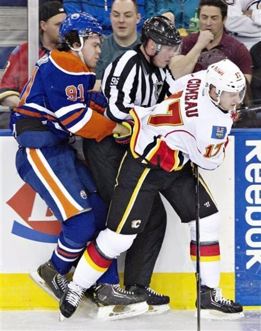Calgary Flames Blake Comeau (17) checks Edmonton Oilers Magnus Paajarvi (91) into linesman David Brisbois during second period NHL hockey action in Edmonton, Alberta, on Monday April 1, 2013. (AP Photo/The Canadian Press, Jason Franson).