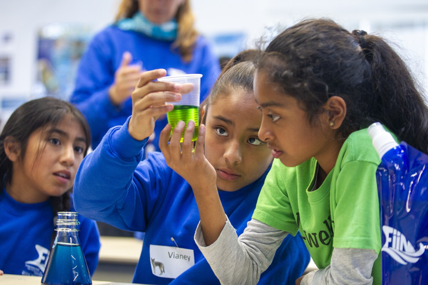 Valeria Pedraza, 11, left, Vianey Olivier, 10, and Kiara Padilla, 10, watch a beaker for a reaction after mixing salt water and fresh water during the FiiN (Fostering interest in Nature) program at the Back Bay Science Center in Newport Beach on Tuesday.