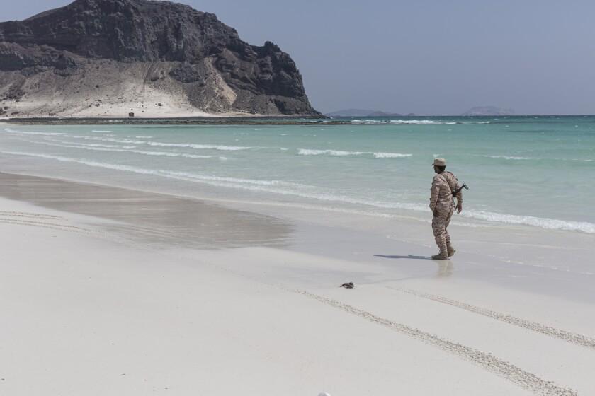 A Yemeni soldier walks along the beach at Bir Ali in Shabwa province, Yemen.