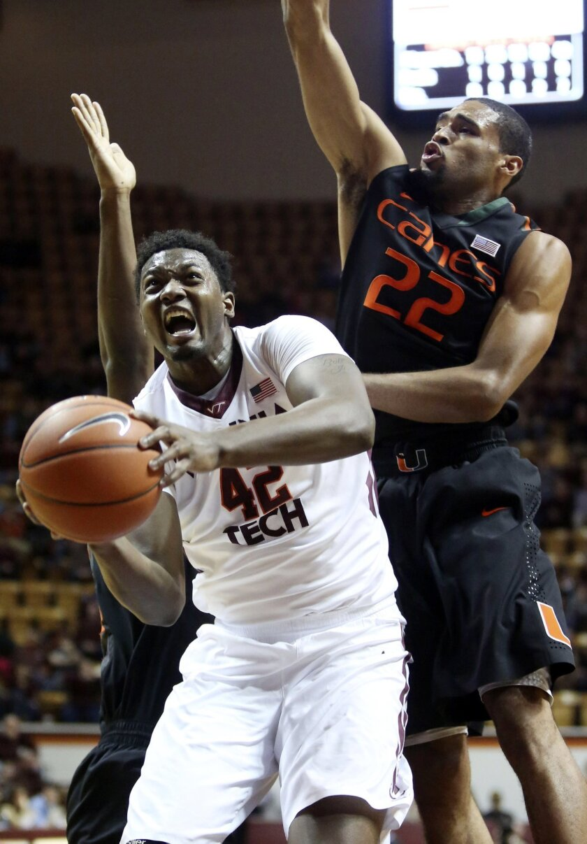 C. J. Barksdale (42) tries to shoot past the defense of Miami's James Kelly, left, and Donnavan Kirk (22) during the first half of an NCAA college basketball game in Blacksburg Va., Saturday, Feb. 15 2014. (AP Photo/The Roanoke Times, Matt Gentry)