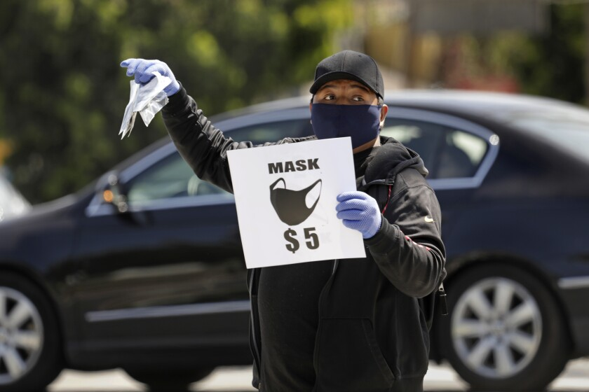 A man sells masks for $5 each on the street in Echo Park on April 3.