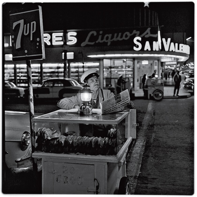 A taco vender catching up on the day's news until the next customer shows up. Gelatin Silver Print, 1964. Photograph by Harry Crosby. Collection of Paul Ganster