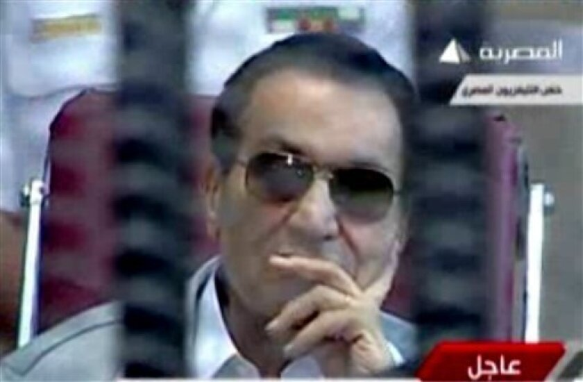 This image made from video broadcast on Egyptian state television shows former President Hosni Mubarak inside the defendant's cage in a courtroom in Cairo, Egypt, Saturday, May 11, 2013. The retrial of former Egyptian President Hosni Mubarak resumed Saturday, with prosecutors requesting to present new evidence from a fact-finding commission's report that claims the ex-leader had full knowledge of the extent of the violence used against protesters. (AP Photo/Egyptian State Television via AP video