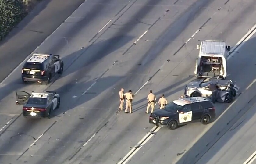 A wrecked car, police officers and emergency vehicles on an empty freeway