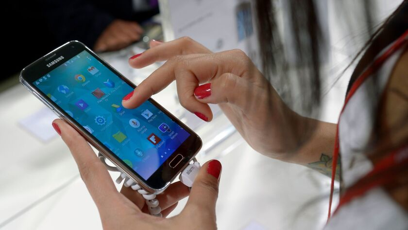 FILE - In this Feb. 25, 2014, file photo, a Samsung Galaxy S5 is demonstrated at the Mobile World Co