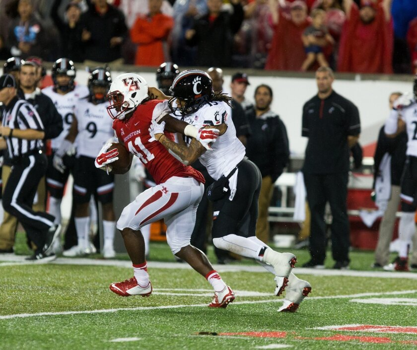 Houston's Steven Taylor (41) is tackled by Cincinnati's Chris Moore (15) after intercepting the ball during the second half of an NCAA college football game at TDECU Stadium, Saturday, Nov. 7, 2015, in Houston. Houston defeated Cincinnati 33-30. (AP Photo/Juan DeLeon)