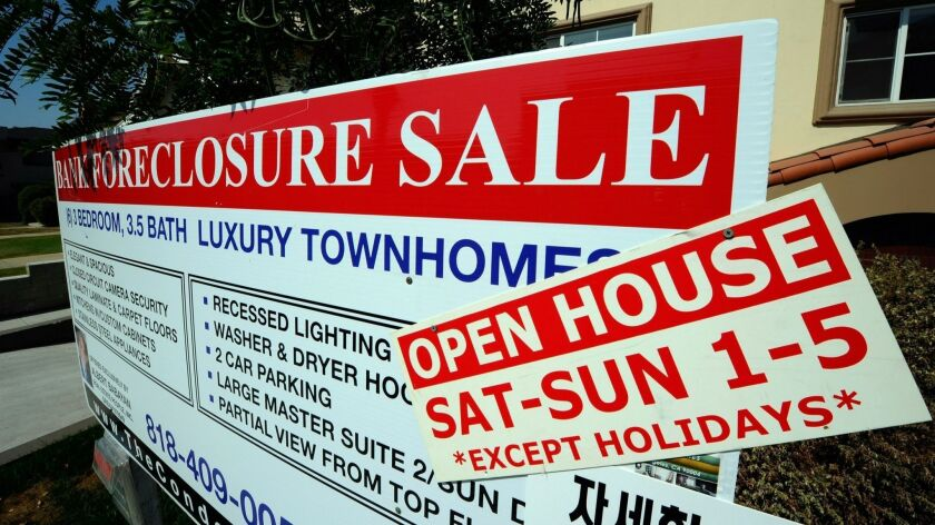 A foreclosure sign is posted in front of town homes in 2010 in Los Angeles. In 2012, Gov. Jerry Brown and the Legislature took $410 million that was supposed to assist victims of abusive mortgage lending and used it to help balance the state budget.