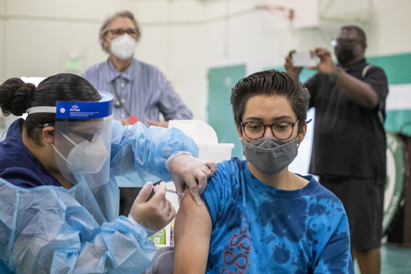 A nurse administers a shot to a student as others look on.