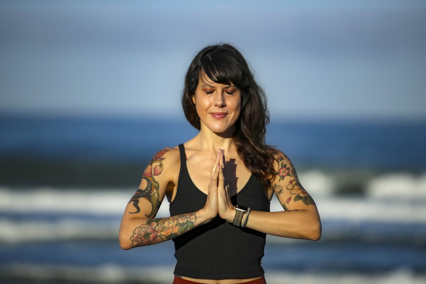 Instructor Laura Schwartz practices yoga on the beach in Carlsbad