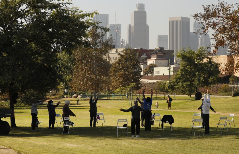 A group of people in masks spaced out in a circle in a park with downtown L.A.'s skyline in the background