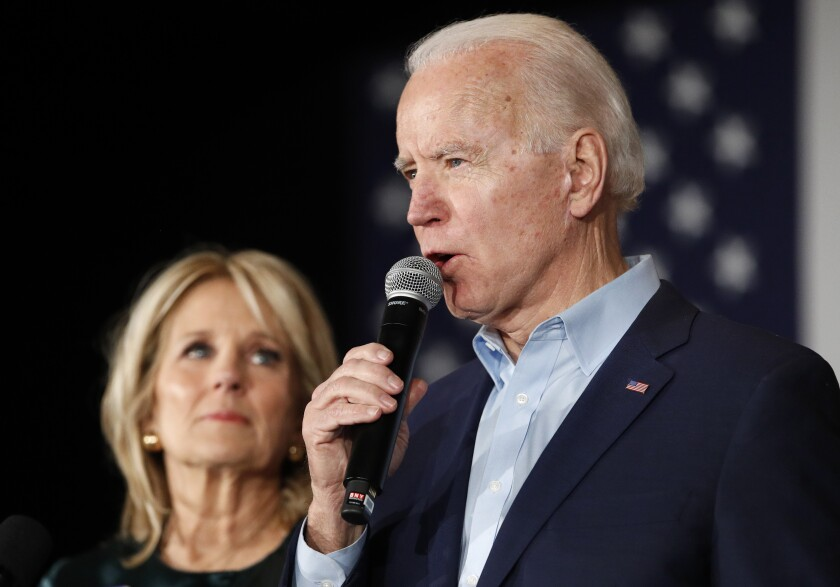 Democratic presidential candidate former Vice President Joe Biden speaks with Jill Biden at a caucus night campaign rally on Monday, Feb. 3, 2020, in Des Moines, Iowa. (AP Photo/John Locher)