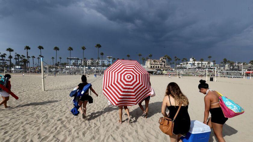 HUNTINGTON BEACH, CALIF. -- TUESDAY, AUG. 1, 2017: Beach goers evacuate the beach as Huntington Beac