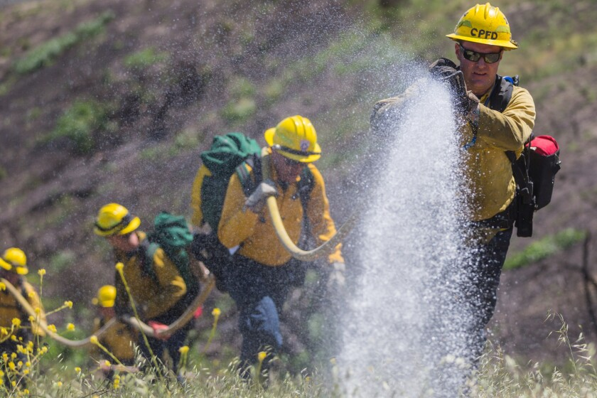 Firefighter Mark Williams, Station 4, Camp Pendleton Fire Department, douses a simulated fire while conducting wild land fire refresher training 130 (WRT) at a mutual threat zone, April 16, 2018. The annual training, held every spring, revolves around a simulated wildfire that firefighters must work together to contain. After the drill, participants discussed which elements went well as well as areas for improvement to ensure readiness for the upcoming fire season. (U.S. Marine Corps photo by Lance Cpl. Kerstin Roberts)