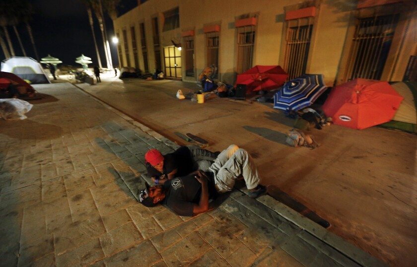 Zac Lee, 25, foreground, and friend Naomi Rosario, 22, who are both homeless, rest on the sidewalk at Venice Beach last month.