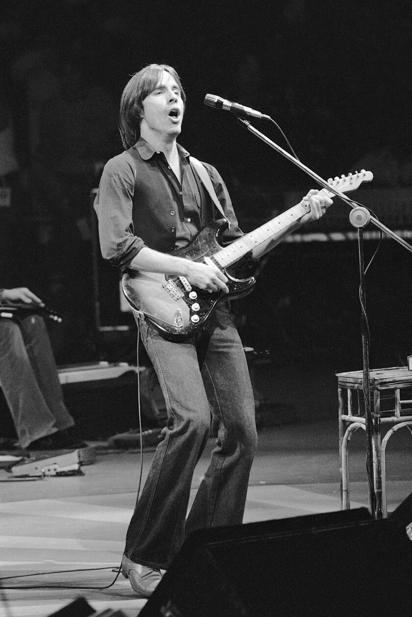 A young man plays the guitar and sings onstage