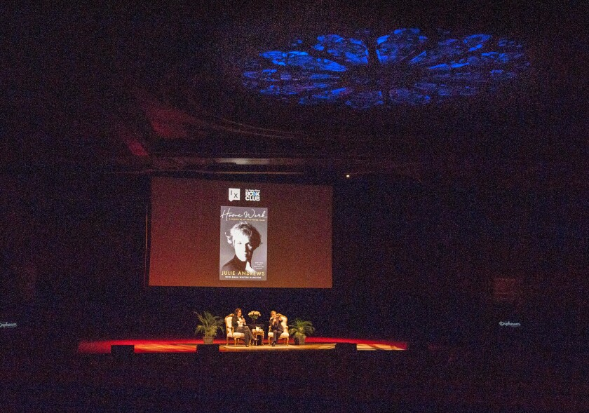 "Mary McNamara, left, and Julie Andrews onstage, with an image of the cover of Andrews' book ""Home Work"" on a screen overhead."