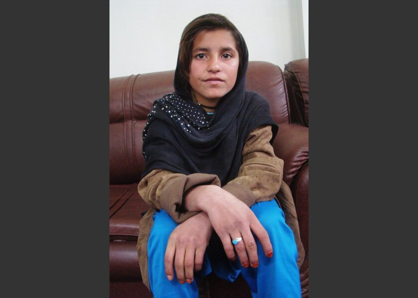 An Afghan girl known as Spozhmai is held in protective custody in Lashkargah, capital of Helmand province, Afghanistan, Wednesday, Jan. 8, 2014. Spozhmai, who authorities say is 10, told police that her brother, who she said is a Taliban commander, wrapped her in an explosives-packed vest but that she refused to blow herself up at a checkpoint in Helmand province. The Taliban denied the alleged plot. (AP Photo/Abdul Khaleq)