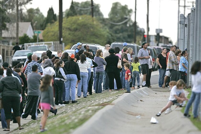 Parents of Millennial Tech Magnet Middle School students waited in line to pick up their children  at an athletic field on the campus of Gompers Prepatory Academy yesterday.