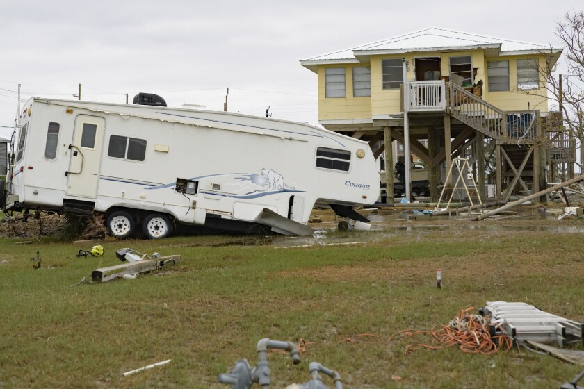 """A camping trailer by a neighboring camp has been damaged by Hurricane Zeta in Grand Isle, La., Friday, Oct. 30, 2020. Gov. John Bel Edwards says the damage from Zeta was """"catastrophic"""" in Grand Isle, a barrier island community south of New Orleans that was one of the hardest-hit areas. (AP Photo/Matthew Hinton)"""