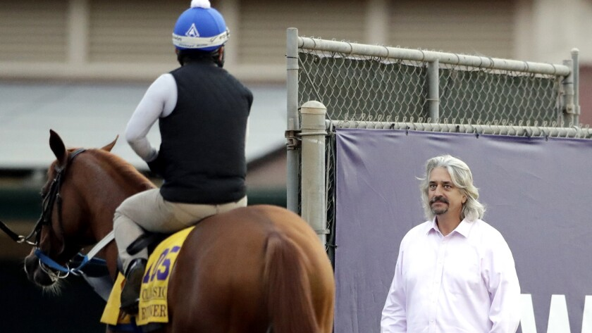 Horse trainer Steve Asmussen, right, looks on as exercise rider Angel Garcia rides Gun Runner during