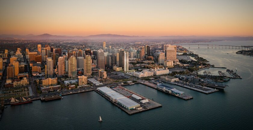 An aerial photo downtown shows Pacific Gate, reflecting a setting sun, superimposed on the skyline just east of the Navy Broadway Complex.