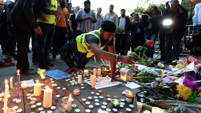epa05984927 People lay tributes at a vigil for the people who lost their lives during the Manchester