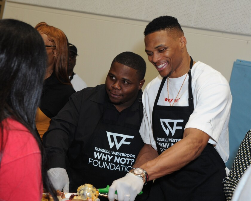 Russell Westbrook is joined by brother Raynard, left, while dishing an early Thanksgiving dinner at Jesse Owens Community Regional Park on Nov. 23.