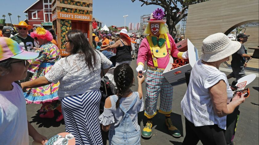 A clown hands out orange sunglasses during opening day for the Orange County Fair in Costa Mesa on F