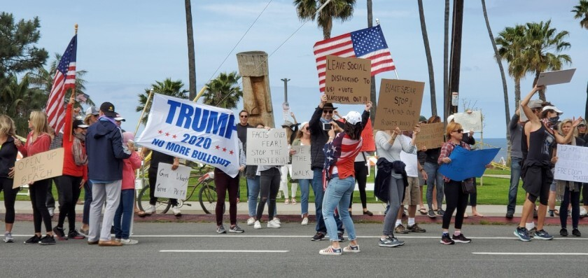 Roughly 200 protesters crowded a roadside in Encinitas on Sunday, April 19, 2020 to call for local officials to reopen beaches and trails.