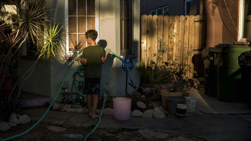 LOS ANGELES, CA - NOVEMBER 21: Caden Schwartz, 9, puts away a garden hose after washing his mother's