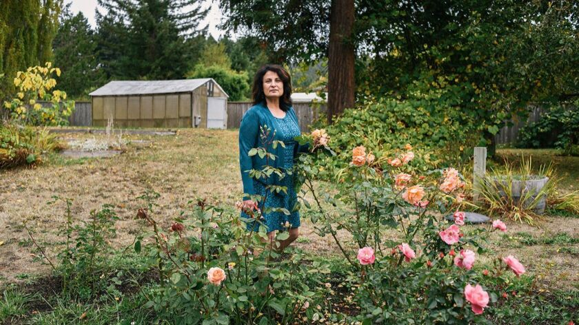 Janet Winston, a professor at Humboldt State University, stands in her rose garden in Eureka, Calif.